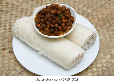 Popular South Indian breakfast puttu / pittu made of steamed rice flour and coconut  in the bamboo mould with spicy Bengal gram curry / utensil, Kerala, India. Bamboo puttu. Sri lankan food