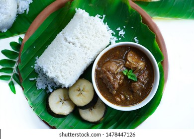 Popular South Indian breakfast steamed rice Puttu with Chicken curry served in banana leaf, selective focus