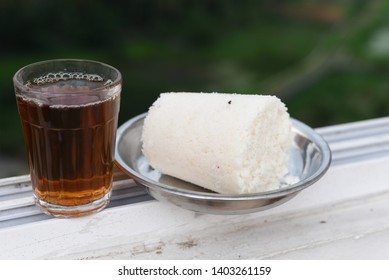 Popular South Indian home made   breakfast puttu or pittu made of steamed rice flour and scraped coconut  in the bamboo mould, with plain tea in Kerala, India. Bamboo puttu. Sri lankan food