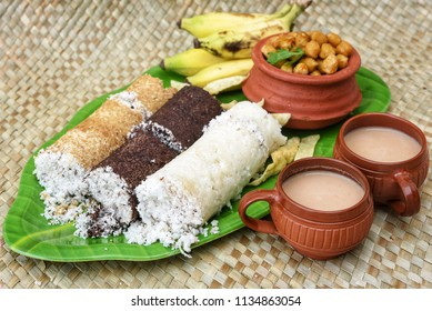 Popular South Indian steamed breakfast Puttu or Pittu made of steamed rice, ragi, wheat flour and coconuvegt  in the bamboo mould with spicy Chana curry, banana and tea Kerala, India. Sri lankan food.