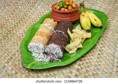 Popular South Indian steamed breakfast Puttu or Pittu made of steamed ragi, wheat flour and grated coconut  in the bamboo mould with spicy Chana curry and banana Kerala, India. Sri lankan food.