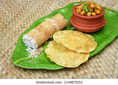 Popular South Indian steamed breakfast Puttu or Pittu made of wheat flour and grated coconut  in the bamboo mould with spicy Chana curry, pappad and banana Kerala, India. Sri lankan food
