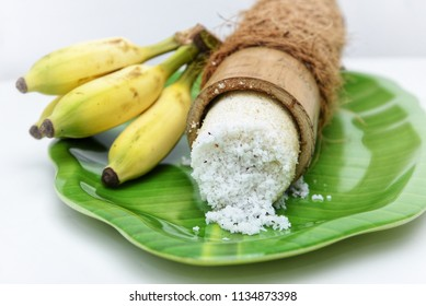 Popular South Indian steamed breakfast Puttu or Pittu made of rice flour and grated coconut  in the bamboo mould with banana Kerala, India. Sri lankan food