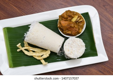 Popular South Indian steamed breakfast dish white Puttu or Pittu made of rice flour and grated coconut  in the bamboo mould with Kozhi Pidi chicken curry Kerala, India. Sri lankan food in banana leaf.