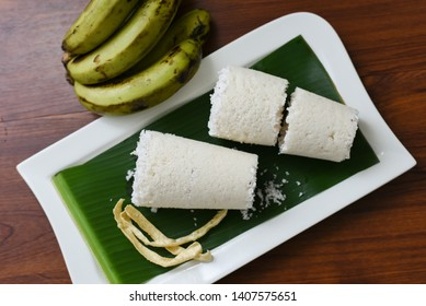 Popular South Indian steamed breakfast dish white Puttu or Pittu made of rice flour and grated coconut  in the bamboo mould with banana Kerala, India. Sri lankan food served in banana leaf.