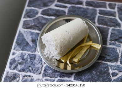 Popular South Indian steamed breakfast dish white Puttu or Pittu made of rice flour and grated coconut  in the bamboo mould in Kerala, India. Sri lankan food served in a stainless steel plate.