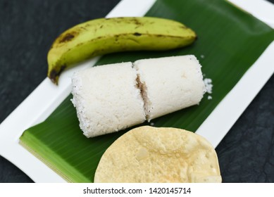 Popular South Indian steamed breakfast dish white Puttu or Pittu made of rice flour and grated coconut  in the bamboo mould with banana and Pappad Kerala, India. Sri lankan food served in banana leaf.