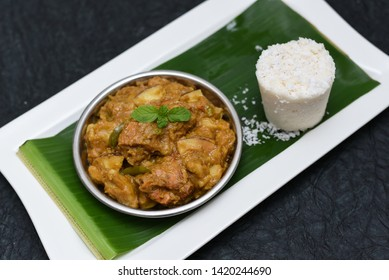 Popular South Indian steamed breakfast dish white Puttu or Pittu made of rice flour, grated coconut in bamboo mould with Malabar style Kozhi Pidi coconut chicken curry, black tea in Kerala, India.