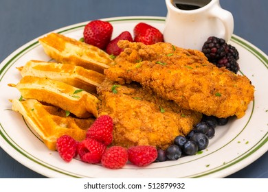 Popular southern dish of fried breaded chicken with waffles, served with berries and maple syrup