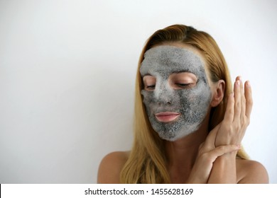 Popular spa treatment bubbling mask with charcoal oxygen purifying product on the face of beautiful girl with long hair. Skin care mask. Funny headband with ears