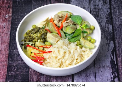 Popular Thai food, Chinese noodle with green chicken curry in coconut milk topped minced pickle lettuce.