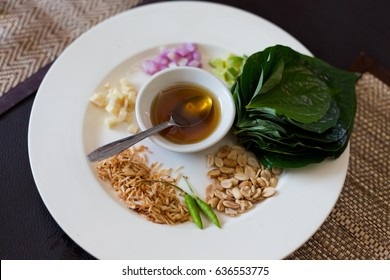 Popular thai snack Miang Kham made of betel leaf, ginger, onion, lime, coconut, peanuts, bird eye chilli and honey. Traditional thai cuisine made of fresh ingredients taken during cooking class.