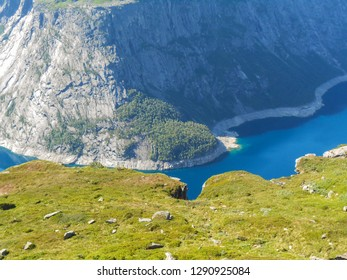 Popular tourist attraction near Trolltunga in sunny weather. View from the Trolltunga trail. Mountain lake Ringedalsvatnet. Norwegian landscape in sunny weather