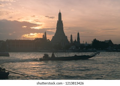 Popular tourist destination and landmark Thai temple Wat Arun in Bangkok, Thailand, view from across the river at sunset with a long tail boat on the river