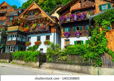 Popular touristic village street view, flowery wooden houses with ornamental gardens and entrances in famous Hallstatt, Salzkammergut region, Austria, Europe