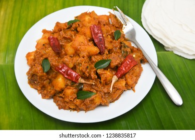 Popular traditional South Indian food  Kappa and appam or tapioca biryani hot and spicy dish made with cooked organic cassava root, grated coconut, beef or steak Kerala, India. staple food of Brazil.