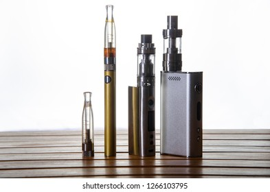 Popular vaping e cig devices mod and pen.electronic cigarette over a wood background. vaporizer e-cig old device model over a white background.