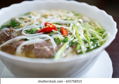 Popular Vietnamese noodle soup pho bo with beef meat & red hot pepper.Close up shot of traditional Asian dish with natural ingredients & spices.Tasty spicy soup from Asia