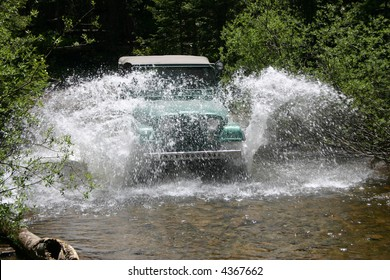 A popular vintage off-road vehicle splashes water over the top while fording  mountain stream.