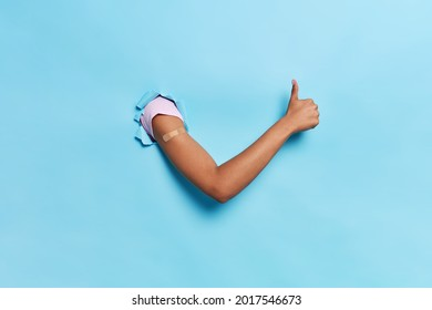 Population immunization health care concept. Unrecognizable person breaks arm through paper blue background shows band aid after vaccination keeps thumb up makes like gesture. After getting vaccine