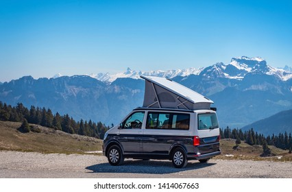 Popup Campervan, Jura, French Alps - May 10, 2019: camping with small lifting roof van in snow covered mountains of France.