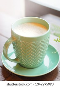 Porcelain aquamarine colored cup with cappuccino. Coffee mug on wooden table. Tasty hot beverage.