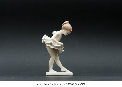 Porcelain ballerina dancer girl figurine isolated on black background