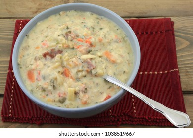 Porcelain blue bowl red placemat spoon over wooden table fresh slow cooked cream soup from potato cubed smocked pork ham celery carrots brown rice red bell pepper seasoned with parsley black pepper