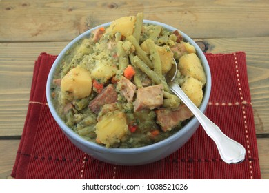 Porcelain blue bowl red placemat spoon wooden table fresh slow cooked stew from cubed yellow potato smocked pork ham green beans seasoned chopped carrots red bell pepper parsley dill black pepper