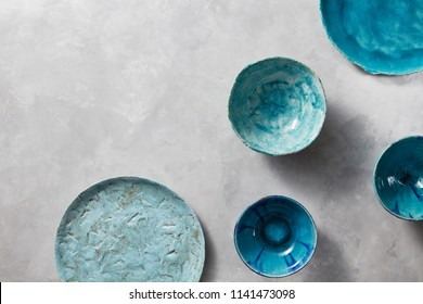 Porcelain blue bowls and plates on a gray marble table. Multi-colored ceramic vintage handmade dishes