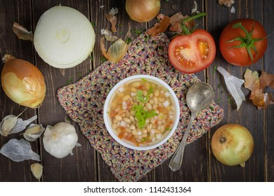 Porcelain bowl full of white beans with tomatoes, onions, parsley and garlic on the wooden table.