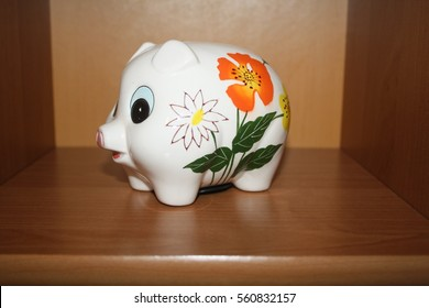 Porcelain colorful pigs for cash registers for money on brown shelf