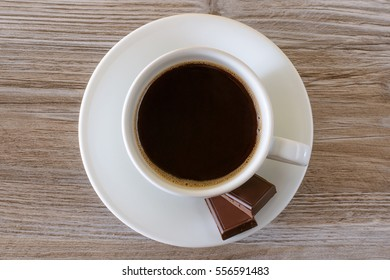 A porcelain  cup of black hot coffee and chocolate