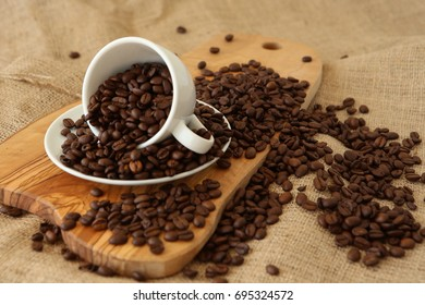 A porcelain cup and coffee beans on the wooden board