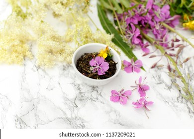 Porcelain Cup with dry herbal Ivan-tea with Fireweed and Meadowsweet on the marble table. Harvesting.