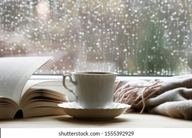 Porcelain cup with hot tea, soft blanket and open book by the window.