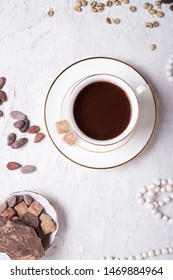 porcelain cup of mocca coffee with natural chocolate, cocao beans, green coffe beans and neck beads around white provence background