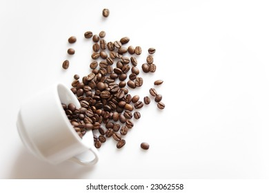 Porcelain cup with sparse coffee beans on white background