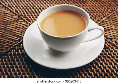 Porcelain cup of tea with milk on wicker background