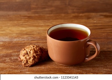 Porcelain cup of tea and sweet cookies on wooden background, top view, selective focus