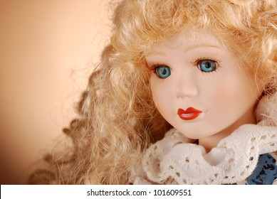 porcelain doll with blonde hair and blue eyes