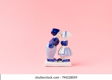 Porcelain figurines of kissing boy and girl in national Dutch costumes on pink background. Saint Valentine's Day Concept.