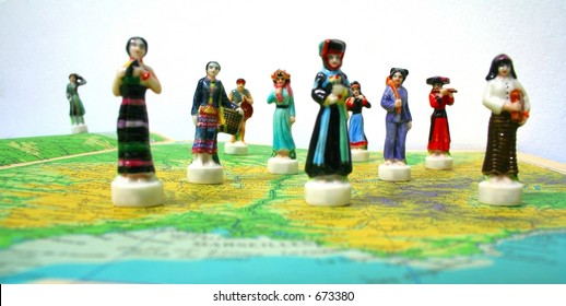 Porcelain figurines on a map, representing people of the world.
