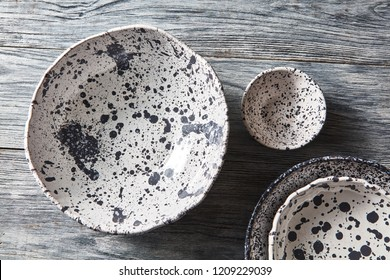 Porcelain gray bowls and plates on a gray wooden table with place for text. Colorful ceramic vintage handmade dishes. Flat lay