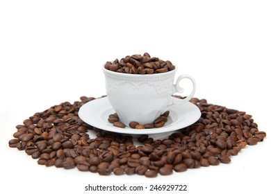 The porcelain mug full of coffee beans isolated on white background