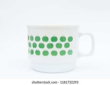 Porcelain mug with little green apple pattern isolated
