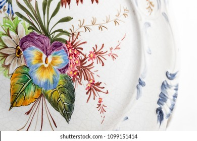 A porcelain plate with floral motifs, hanging on the wall inside a kitchen.