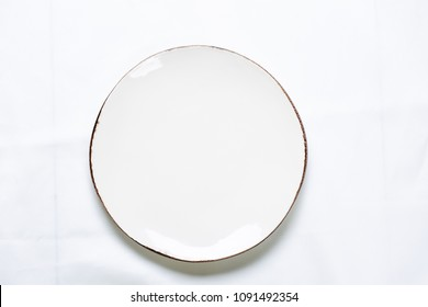 Porcelain plate on a white tablecloth. Flat lying empty plate with place for copy.