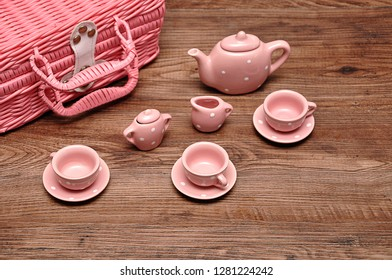 A porcelain spotted tea set with a pink basket