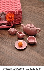 A porcelain spotted tea set with a pink basket and an orange rose